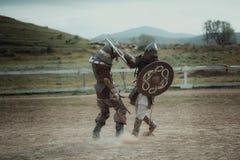 Μεσαιωνικοί ιππότες κονταροχτυπήματος στα κράνη και μάχη ταχυδρομείου αλυσίδων στο ξίφος στοκ εικόνα