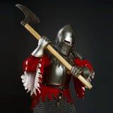 Μεσαιωνικός ιππότης με ένα τσεκούρι στο γκρίζο υπόβαθρο Στοκ φωτογραφία με δικαίωμα ελεύθερης χρήσης