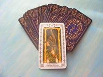 Μεσαιωνικός στενός επάνω καρτών Tarot με το ρωσικό τίτλο το Hangedman, οι κρεμασμένες γέφυρες Tarot ατόμων στο μπλε ξύλινο υπόβαθ στοκ εικόνα με δικαίωμα ελεύθερης χρήσης