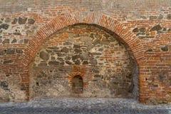 Μεσαιωνικός τοίχος τούβλου και πετρών με μια αψίδα Στοκ Εικόνες
