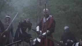 Μεσαιωνικό στρατιωτικό στρατόπεδο με τους ανθρώπους στο τεθωρακισμένο με τα όπλα που εκπαιδεύουν, δάσος smokey απόθεμα βίντεο
