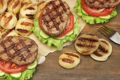 Μεσημεριανό γεύμα με τα σπιτικά ψημένα στη σχάρα BBQ χάμπουργκερ στον πίνακα πικ-νίκ Στοκ εικόνα με δικαίωμα ελεύθερης χρήσης