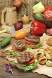 Μεσημεριανό γεύμα με τα σπιτικά ψημένα στη σχάρα BBQ χάμπουργκερ στον πίνακα κουζινών Στοκ εικόνες με δικαίωμα ελεύθερης χρήσης