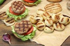 Μεσημεριανό γεύμα με τα σπιτικά ψημένα στη σχάρα BBQ χάμπουργκερ στον πίνακα πικ-νίκ Στοκ εικόνες με δικαίωμα ελεύθερης χρήσης