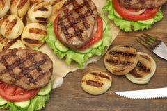 Μεσημεριανό γεύμα με τα σπιτικά ψημένα στη σχάρα BBQ χάμπουργκερ στον πίνακα κουζινών Στοκ Εικόνα