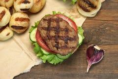 Μεσημεριανό γεύμα με τα σπιτικά ψημένα στη σχάρα BBQ χάμπουργκερ στον πίνακα πικ-νίκ Στοκ φωτογραφία με δικαίωμα ελεύθερης χρήσης