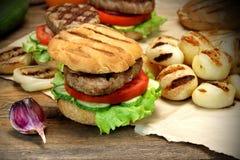 Μεσημεριανό γεύμα με τα σπιτικά ψημένα στη σχάρα BBQ χάμπουργκερ στον πίνακα κουζινών Στοκ Εικόνες