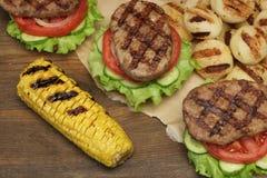 Μεσημεριανό γεύμα με τα σπιτικά ψημένα στη σχάρα BBQ χάμπουργκερ στον πίνακα πικ-νίκ Στοκ Εικόνα