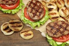 Μεσημεριανό γεύμα με τα σπιτικά ψημένα στη σχάρα BBQ χάμπουργκερ στον πίνακα πικ-νίκ Στοκ Φωτογραφία