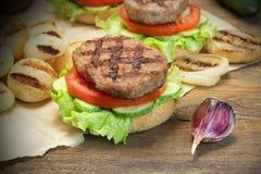 Μεσημεριανό γεύμα με τα σπιτικά ψημένα στη σχάρα BBQ χάμπουργκερ στον πίνακα κουζινών Στοκ Φωτογραφία