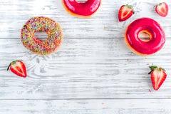 Μεσημεριανό γεύμα με τα donuts και φράουλα στην ξύλινη χλεύη άποψης επιτραπέζιου υποβάθρου τοπ επάνω Στοκ Φωτογραφίες