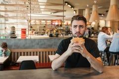 Μεσημεριανό γεύμα στον καφέ Κοιτάζει άμεσα, κρατώντας burger στο χέρι του στοκ εικόνες με δικαίωμα ελεύθερης χρήσης