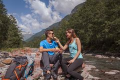 Μεσημεριανό διάλειμμα ζευγών Backpackers με το landjaeger και το ψωμί σε έναν ποταμό στοκ εικόνες με δικαίωμα ελεύθερης χρήσης
