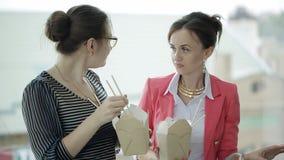 Μεσημεριανό διάλειμμα στο γραφείο Δύο επιχειρησιακές γυναίκες τρώνε τα κινεζικά νουντλς και επικοινωνούν τη στάση στο παράθυρο φιλμ μικρού μήκους
