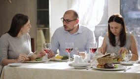 Μεσημεριανό διάλειμμα στο εστιατόριο στην επιχείρηση των καλύτερων φίλων Άνδρας και δύο γυναίκες που έχουν το μεσημεριανό γεύμα σ απόθεμα βίντεο