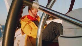 Μεσογειακός - το Νοέμβριο του 2017 circa: Το καυκάσιο άτομο κάθεται στο πιλοτήριο του πλέοντας γιοτ απόθεμα βίντεο