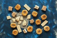Μεσο-Ανατολικά γλυκά τρόφιμα σε ένα μπλε υπόβαθρο, τοπ άποψη Baklava, halva, sherbet, σουσάμι με το μέλι Στοκ Φωτογραφίες