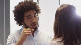 Μεσο-Ανατολικό άτομο που έχει μια συνομιλία με τη γυναίκα συνάδελφος στην αρχή απόθεμα βίντεο