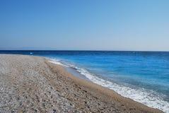 Μεσόγειος ακτών παραλία χαλικιών στην ηλιόλουστη ημέρα Στοκ Εικόνες