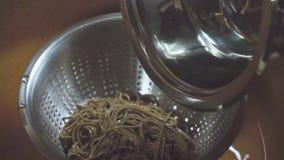 Μετάγγιση των νουντλς φαγόπυρου με το νερό από ένα κύπελλο γυαλιού σε ένα τρυπητό φιλμ μικρού μήκους