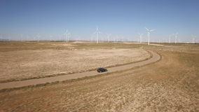 Μετά από ένα μαύρο αυτοκίνητο στο αγρόκτημα ανεμόμυλων, κυρτός δρόμος απόθεμα βίντεο