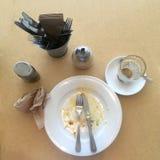 Μετά από τον πυροβολισμό Τοπ άποψη που εξετάζει κάτω το τελειωμένα πιάτο και το γυαλί μετά από να φάει το υγιές πρόγευμα Στοκ Φωτογραφίες