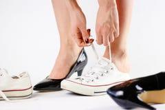 Μεταβαλλόμενα παπούτσια κοριτσιών Αφαιρεί τα μαύρα παπούτσια και φορά το άσπρο πάνινο παπούτσι Στοκ Φωτογραφίες