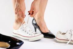 Μεταβαλλόμενα παπούτσια κοριτσιών Αφαιρεί τα μαύρα παπούτσια και φορά το άσπρο πάνινο παπούτσι Στοκ φωτογραφία με δικαίωμα ελεύθερης χρήσης