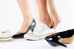 Μεταβαλλόμενα παπούτσια κοριτσιών Αφαιρεί τα μαύρα παπούτσια και φορά το άσπρο πάνινο παπούτσι Στοκ Εικόνες