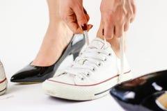 Μεταβαλλόμενα παπούτσια κοριτσιών Αφαιρεί τα μαύρα παπούτσια και φορά το άσπρο πάνινο παπούτσι Στοκ φωτογραφίες με δικαίωμα ελεύθερης χρήσης