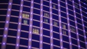 Μεταβαλλόμενες πολύχρωμες λάμπες φωτός στα παράθυρα ενός ουρανοξύστη απόθεμα βίντεο