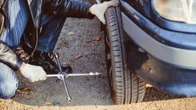 Μεταβαλλόμενη ρόδα ατόμων σε ένα αυτοκίνητο Στοκ Εικόνες