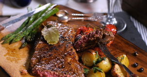 Dolly close up push in view of a sirloin steak with asparagus, potatoes and roasted tomatoes Stock Footage