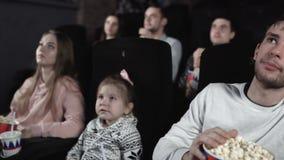 Μετακινηθείτε την κίνηση των ανθρώπων τρώει popcorn και προσέχει έναν κινηματογράφο στον κινηματογράφο απόθεμα βίντεο
