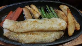 Μετακινηθείτε την μπριζόλα ψαριών με το λαχανικό που τηγανίζεται Στοκ Εικόνες