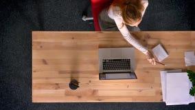 Μετακινηθείτε τον πυροβολισμό, την κορυφή κάτω από την άποψη της κοκκινομάλλους εργασίας γυναικών με τον υπολογιστή, την ομιλία σ φιλμ μικρού μήκους