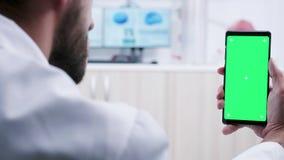 Μετακινηθείτε τον πυροβολισμό του ιατρικού προσωπικού που κρατά ένα smartphone με μια πράσινη οθόνη απόθεμα βίντεο