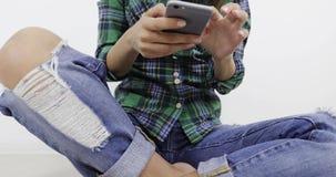 Μετακινηθείτε τον πυροβολισμό Το νέο όμορφο κορίτσι κάθεται στο σπίτι στο πάτωμα και τρύπημα του κειμένου σε ένα κινητό τηλέφωνο απόθεμα βίντεο