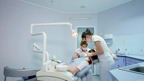 Μετακινηθείτε τον πυροβολισμό του οδοντιάτρου που εξετάζει τη στοματική κοιλότητα ενός ασθενή με τον πονόδοντο απόθεμα βίντεο