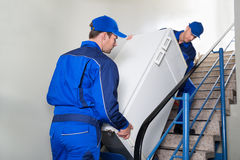 Μετακινούμενοι που φέρνουν το ψυγείο στα βήματα Στοκ εικόνα με δικαίωμα ελεύθερης χρήσης