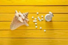 Μεταλλεύματα για την υγεία και την ομορφιά Ταμπλέτες του ασβεστίου, κοχύλι στον κίτρινο ξύλινο πίνακα Τοπ όψη ΙΑΤΡΙΚΗ έννοια Στοκ Εικόνες