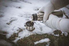 Μεταλλικά, λαμπρά thermos με τον καυτό καφέ snowdrift Μια κούπα του τσαγιού στο χιόνι Πεζοπορία, που περπατά στα ξύλα, υπόλοιπο στοκ εικόνες