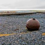 Μεταλλικός σημαντήρας σε μια παραλία βοτσάλων Στοκ Εικόνες