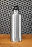 Μεταλλικό μπουκάλι νερό και carabiner στο ξύλινο υπόβαθρο ραφιών Μονωμένο εμπορευματοκιβώτιο για το σχέδιό σας στοκ εικόνες