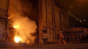 Μεταλλουργός στην εργασία από το furnance, το σίδηρο και τις χαλυβουργικές εργασίες φυσήματος απόθεμα βίντεο