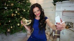 Μεταμφίεση, κινητό τηλέφωνο στα χέρια μιας νέας γυναίκας που κάνει το κορίτσι φωτογραφιών σε μια γιορτή Χριστουγέννων κοντά στο χ απόθεμα βίντεο