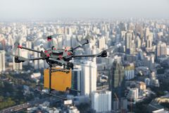 Μεταφορά κηφήνων που πετά με το κουτί από χαρτόνι επάνω από την πόλη στοκ εικόνα