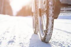 Μεταφορά μωρών με τις διογκώσιμες ρόδες στο δρόμο χειμερινού χιονιού κάτω από το φωτεινό ήλιο στην ελαφριά ημέρα Στοκ Εικόνα