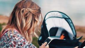 Μεταφορά μωρών ταλάντευσης μητέρων στον πάγκο και τη χρησιμοποίηση του smartphone θερινό ηλιόλουστο swallowtail χλόης ημέρας πετα απόθεμα βίντεο