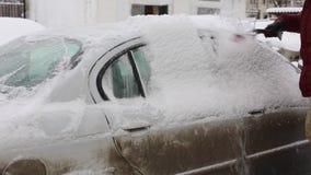 Μεταφορά, χειμώνας, καιρός, άνθρωποι και έννοια οχημάτων - καθαρίζοντας χιόνι ατόμων από το αυτοκίνητο με τη βούρτσα στο σπίτι δι απόθεμα βίντεο